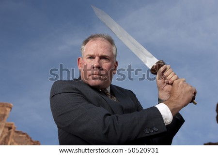 Businessman gives an intense look as he holds a sword, ready to battle. Horizontal shot.