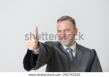 Businessman giving a thumbs up gesture of success, support, voting yes or signalling his agreement