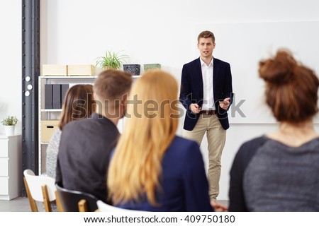Businessman giving an explanation as he stands doing a presentation to his business team or group of co-workers, view from behind their backs #409750180