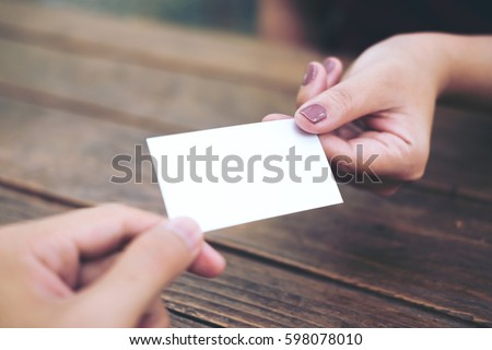 Businessman giving  business card to businesswoman with wooden table background #598078010