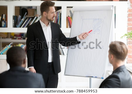 Businessman giving flipchart presentation explaining idea to diverse partners, business coach teaching employees on whiteboard at corporate training, serious ceo explains project to multiracial team