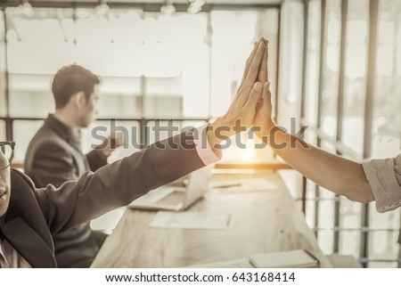 businessman giving hi five/ touching hands and thumb up during meeting for celebration business achievement and success with teamwork #643168414