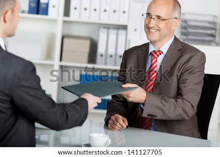 Businessman giving his job application to the employer inside the office