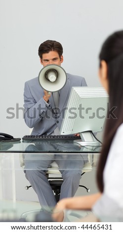 Businessman giving instructions with a megaphone in the office