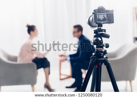 businessman giving interview to journalist in office, camera on tripod on foreground