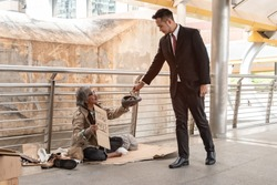Businessman giving money to pity beggar. Rich man donate one dollar banknote to homeless who wearing sweater, sitting on walkway and suffering from cold weather. Sharing concept.