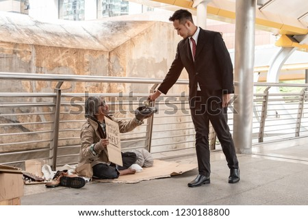 Businessman giving money to pity beggar. Rich man donate one dollar banknote to homeless who wearing sweater, sitting on walkway and suffering from cold weather. Sharing concept. Stock photo ©