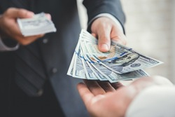 Businessman giving or paying money to a man, US dollar (USD) bills - lending, loan and financial concepts