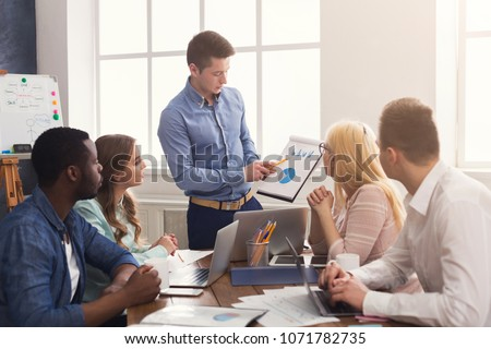 Businessman giving presentation to colleagues in modern office. Young business team discussing new marketing strategy, planning startup project, copy space