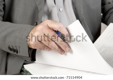 Businessman going through contract pages before to sign it. Focus on hand with a pen and pages.
