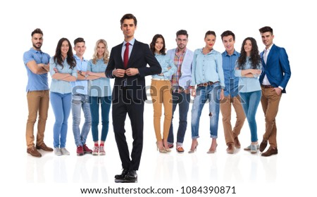 businessman group leader buttoning suit jacket in front of his casual team while standing on white background #1084390871