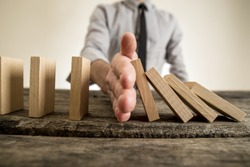 Businessman halting the domino effect inserting his hand between falling and upright wooden blocks in a close up conceptual image.