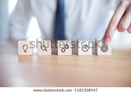 Businessman hand arranging wood block with icon business strategy and Action plan. #1182308947