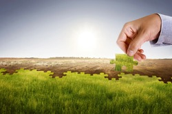 Businessman hand assemble puzzle to build new world with fresh environment. Climate change concept.
