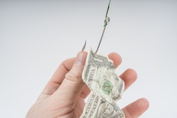 Businessman hand caught on a fishing hook with bait dollars money banknote. Business concept idea. fraud, risk, danger, bribe