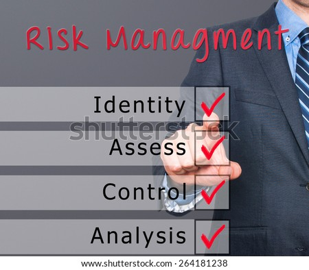 Businessman hand checking the checklist boxes risk management identity assess control analysis by pen on transparent glass. Isolated on grey background. Stock Iamge