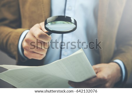 Businessman hand document and magnifier in office #642132076