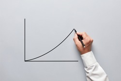 Businessman hand drawing a chart or line graph with an increasing slope on gray background.
