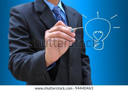 businessman hand drawing a light bulb