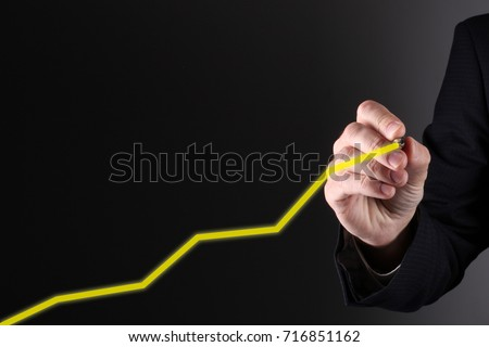 Businessman hand drawing a line graph.