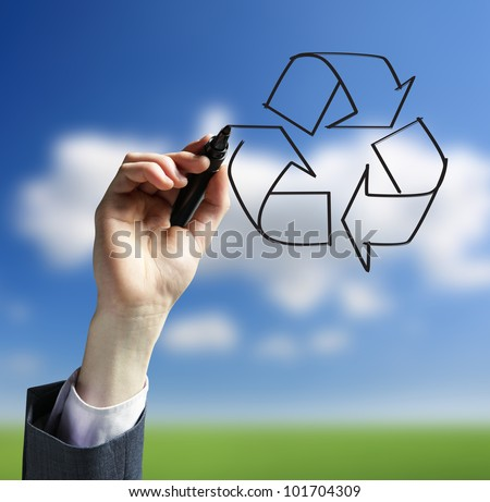 Businessman hand drawing a recycling logo