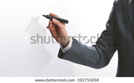 Businessman hand drawing in a whiteboard, copy space