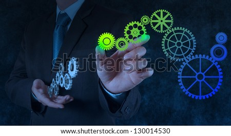 businessman hand draws gear to success concept on touch screen computer