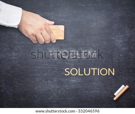 Businessman hand erased the word PROBLEM from a chalkboard for changing to SOLUTION. Change concept.