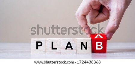 Photo of  Businessman hand flipping wooden cube blocks with PLAN A change to PLAN B text on table background. strategy, analysis, marketing, project and Crisis concepts