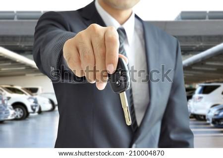 Businessman hand giving a car key - car sale & rental business concept