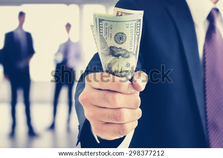 Businessman hand gripping money, US dollar (USD) bills, vintage tone - investment, success and profitable business concepts