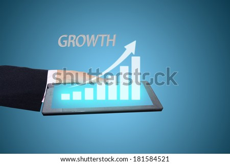 businessman hand holding a growth graph on tablet.