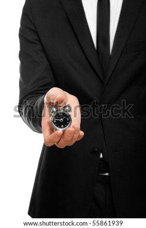 businessman hand holding a small alarm clock, isolated on white