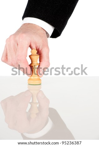 businessman hand holding a white king from chess game - stock photo