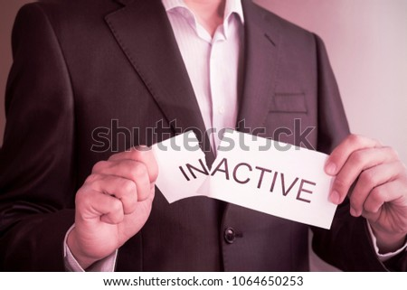 businessman Hand holding card with text inactive, tearing off word in so it written active. Conceptual image of changing his position from inactive to active.