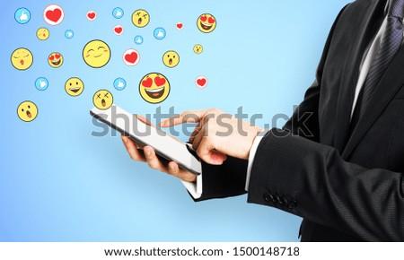 Businessman hand holding cellphone with emotive smileys on subtle background. Communication and emotion concept