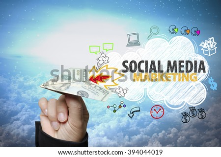 businessman hand holding dollar plane with SOCIAL MEDIA MARKETING text ,business idea , business concept