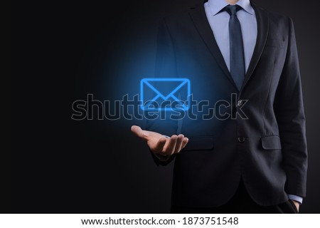 Businessman hand holding e-mail icon, Contact us by newsletter email and protect your personal information from spam mail. Customer service call center contact us concept. Photo stock ©
