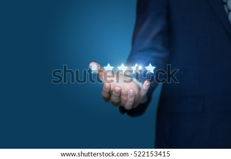 Businessman hand holding five stars isolated on blue background. #522153415