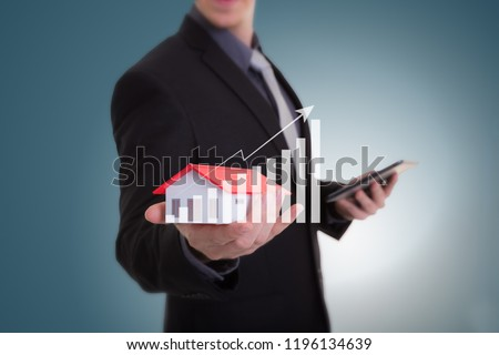 Businessman hand holding house representing home ownership and the Real Estate business with tablet. Mortgage concept