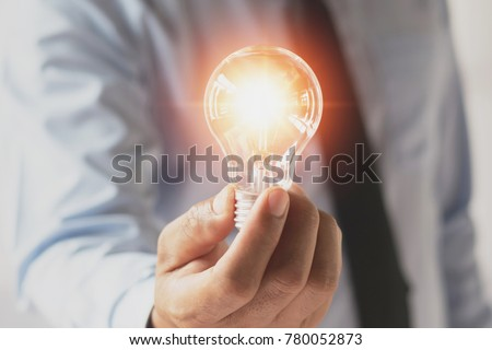 businessman hand holding light bulb. idea concept with innovation and inspiration #780052873