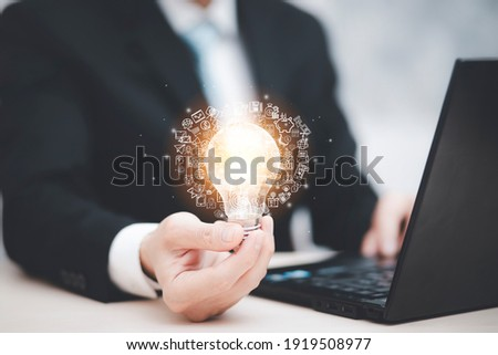 Businessman hand holding light bulb with icons and working on the desk, Creativity and innovation are keys to success.Concept of new idea and innovation with energy and power , working at home,