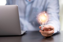 Businessman hand holding lightbulb with orange glowing for creative thinking idea concept.