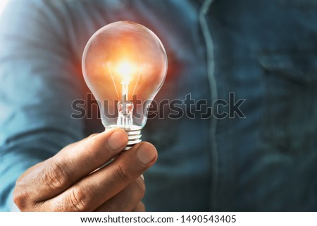 businessman hand holding lightbulb with sunshine. concept saving energy power