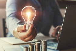 businessman hand holding lightbulb with using laptop and money stack in office. idea saving energy and accounting finance concept
