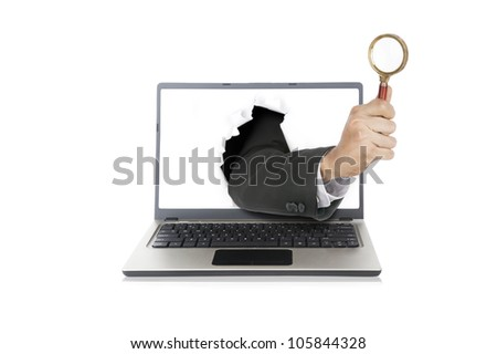 Businessman hand holding magnifying out from laptop computer
