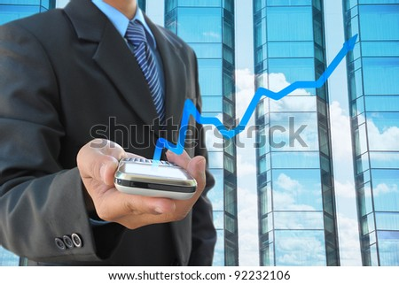 businessman hand holding mobile phone and business graph