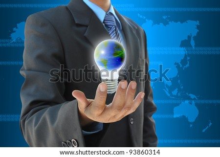 businessman hand holding the world in light bulb