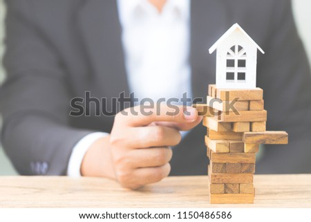 Businessman hand holding wood block with model white house. Investment risk and uncertainty in the real estate housing market. Property investment and house mortgage financial concept. with copy space