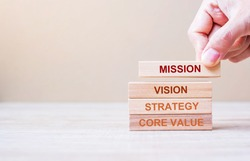 Businessman hand holding wooden building blocks with MISSION, VISION, CORE VALUE and STRATEGY word. Business concepts